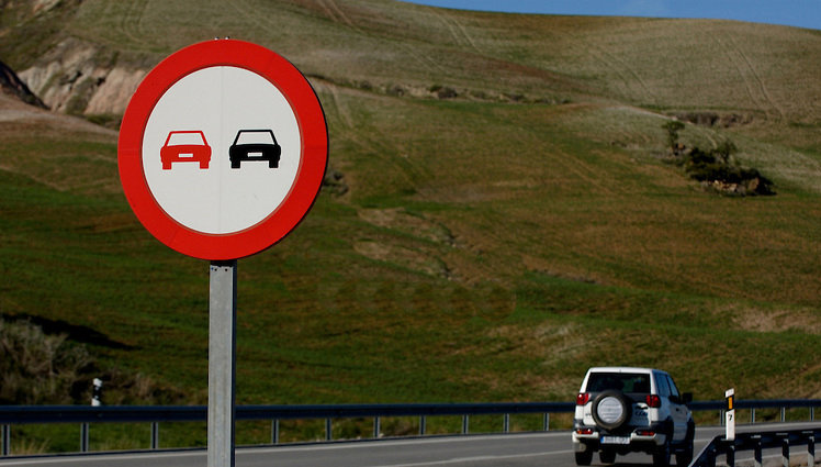 Знак обгон запрещен и машина на дороге